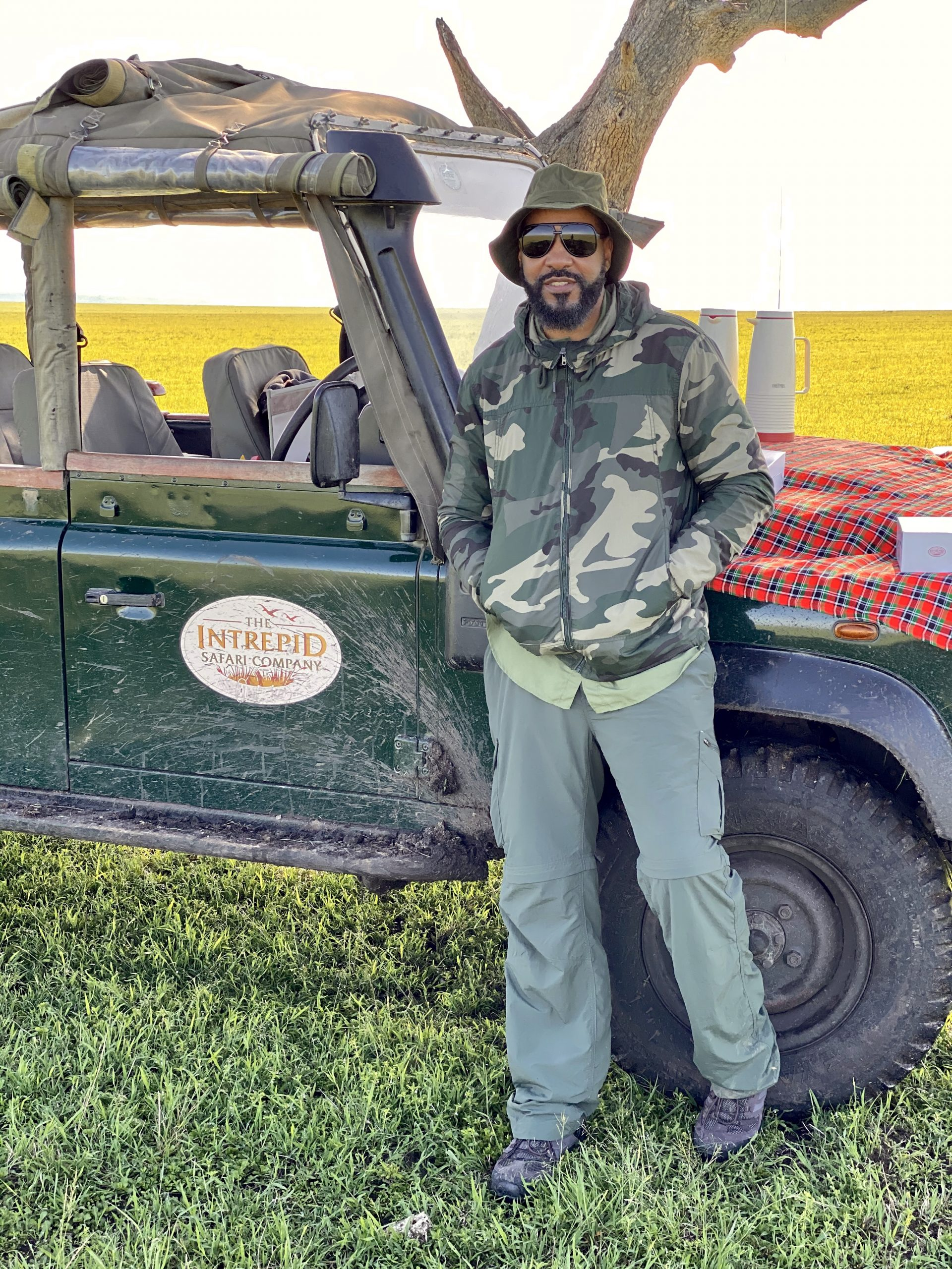 man with cap posing beside muddy jeep