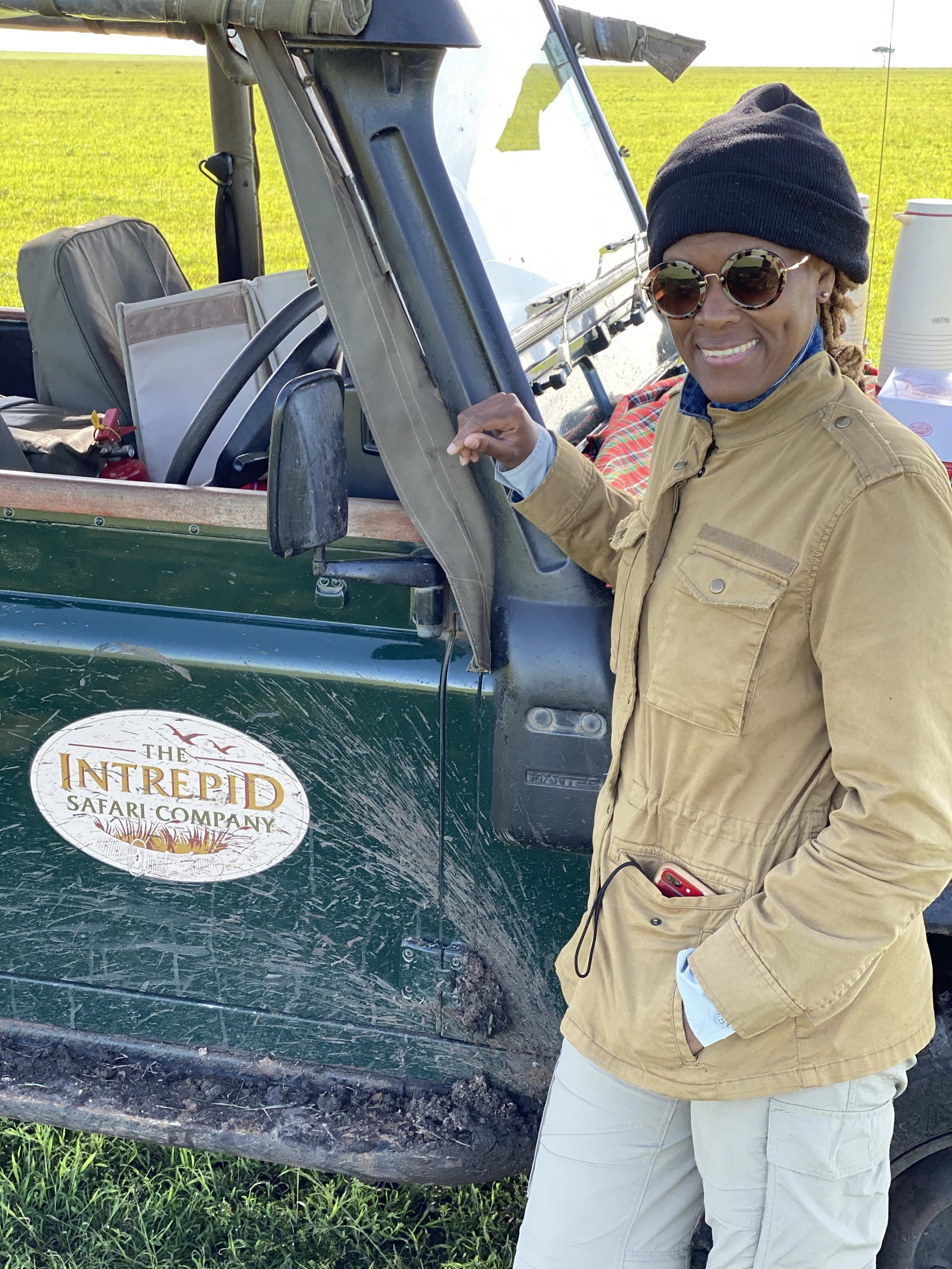 woman with cap posing beside muddy jeep