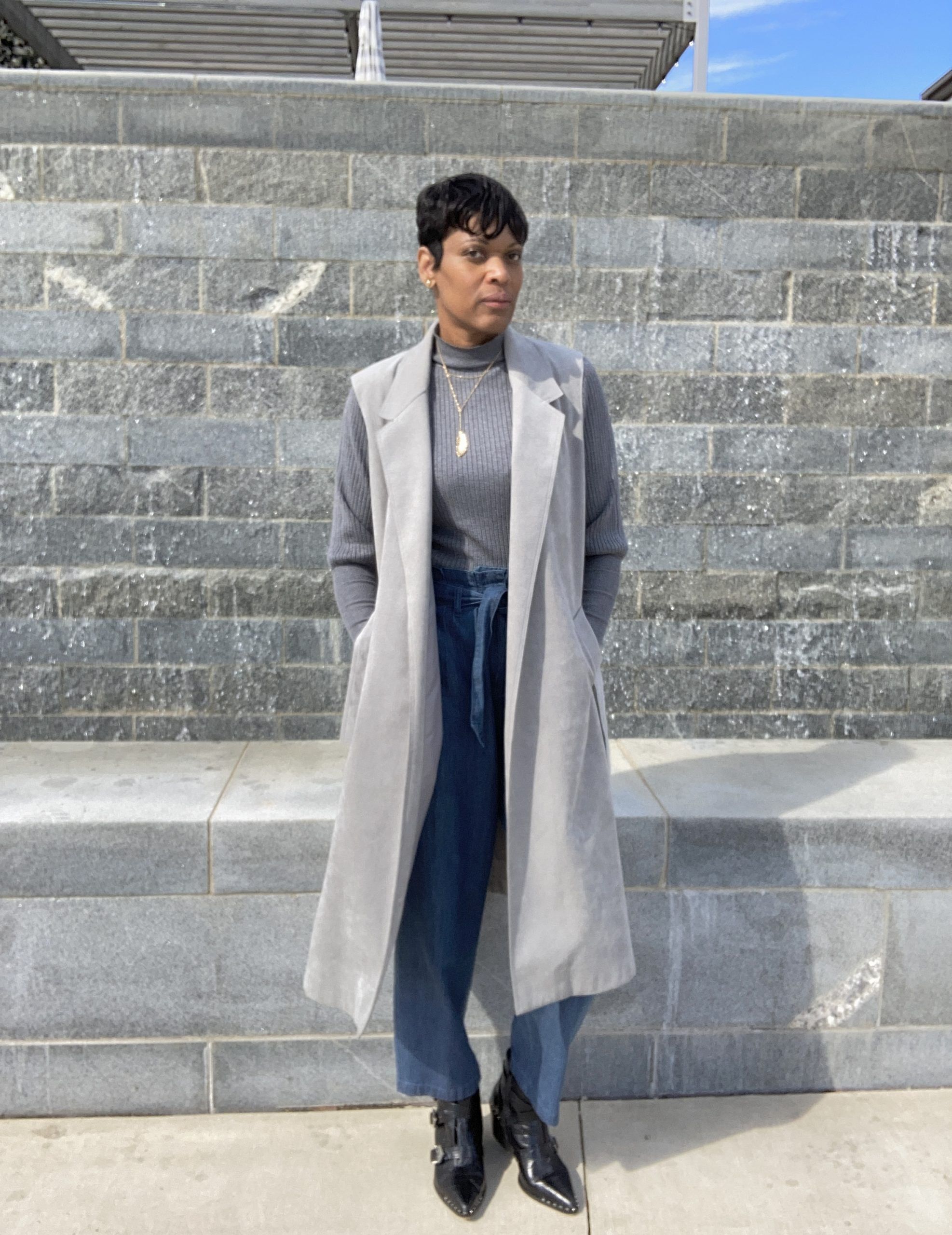 woman posing in open belted trench coat