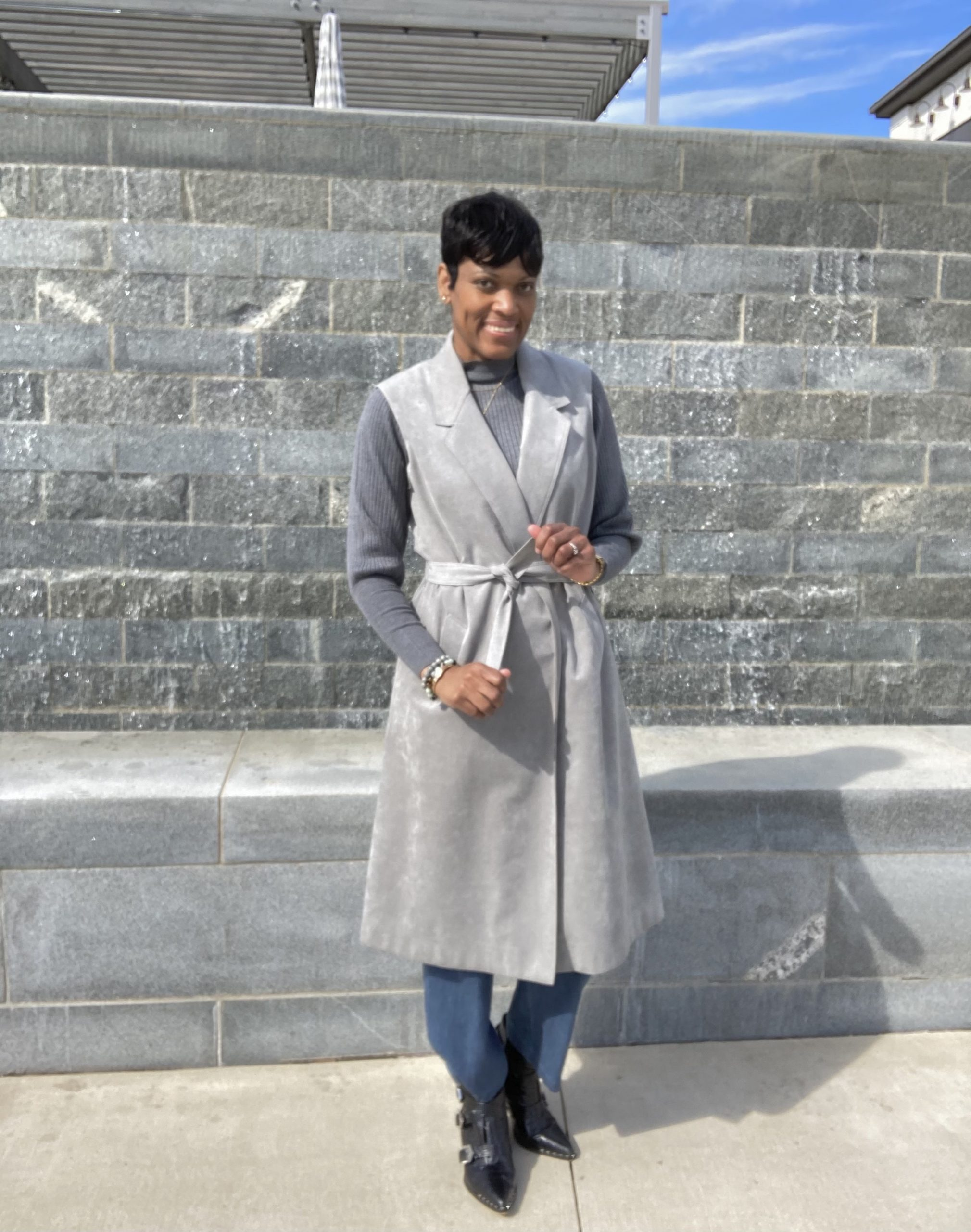 woman posing in closed belted trench coat