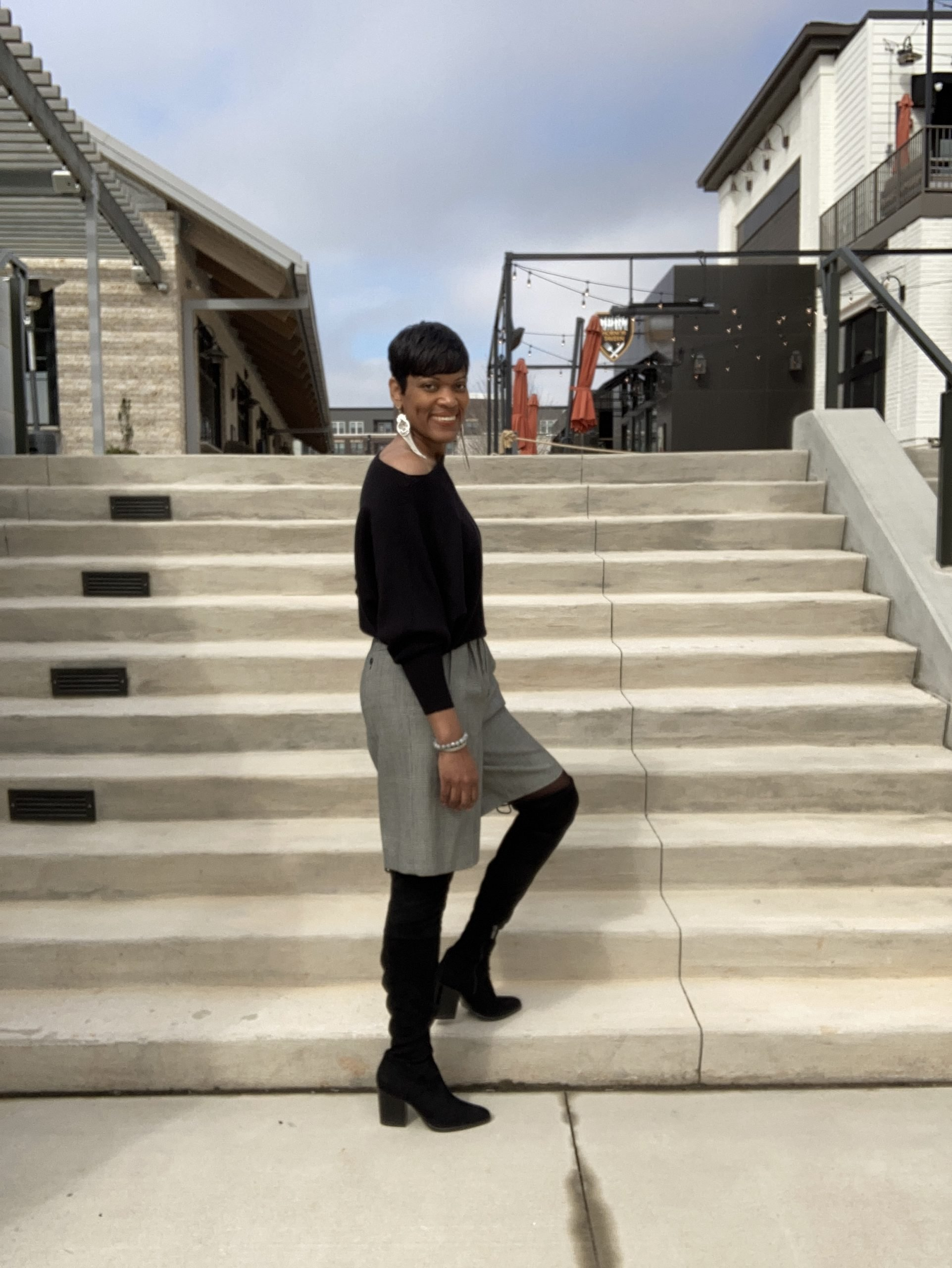 woman posing in thrifted shorts on stairs